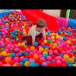 Kids indoor playground with many toys : balls, sliders, baloons. Kids playing