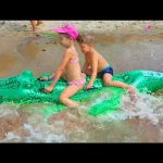 Kids playing on the beach with funny inflatable crocodile