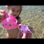 Kids playing on the beach . They making ice cream and cakes from sand. Video 2016